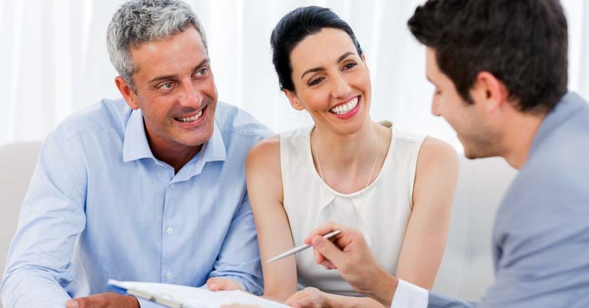 Husband in blue shirt and Wife in white shirt going over paper work with a Client Consultant wearing a light blue tux