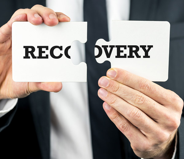 A Man holding puzzle pieces together one in his right and and one in his left hand with the word recovery on it.